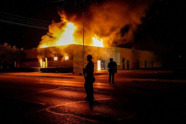 PHOTO: Police stand near a department of corrections building that was on fire during protests, Monday, Aug. 24, 2020, in Kenosha, Wis., sparked by the shooting of Jacob Blake by a Kenosha Police officer a day earlier. (Morry Gash/AP)