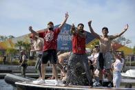 Tampa Bay Buccaneers NFL football tight end Tanner Hudson left, wide receiver Mike Evans, middle, and wide receiver Scott Miller celebrate their Super Bowl 55 victory over the Kansas City Chiefs with a boat parade in Tampa, Fla., Wednesday, Feb. 10, 2021. (AP Photo/Phelan Ebenhack)