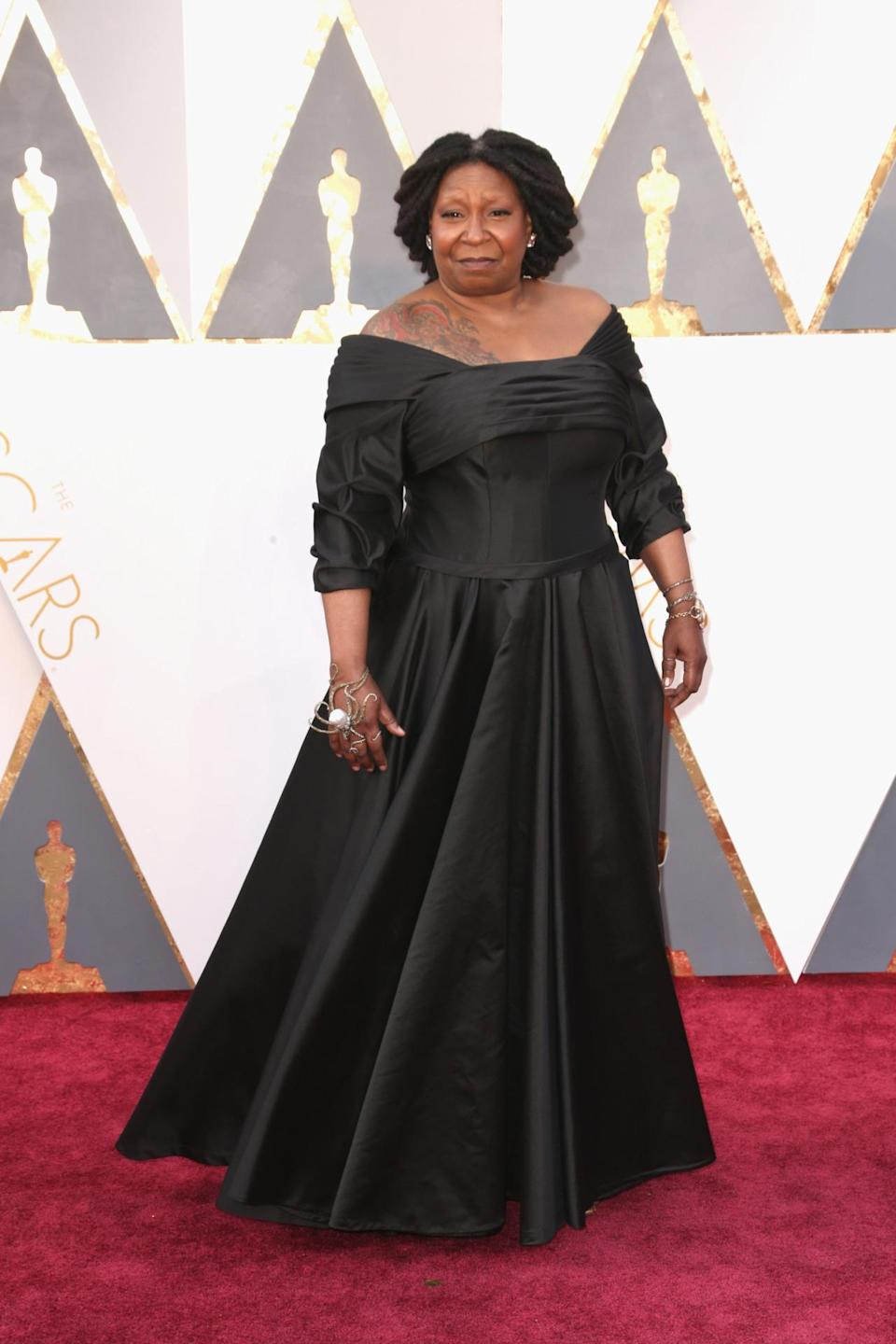 <p>Whoopi Goldberg, who showed off a large shoulder tattoo that the world didn't really know about, wore a black gown custom-made for her by Deadly Dames. The look was inspired by a dress Bette Davis wore in <i>All About Eve</i>. She paired the sophisticated dress with some kooky octopus rings. <i><i>(Photo: Getty Images)</i></i></p>