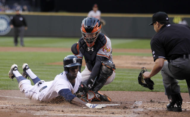 Seattle Mariners' James Jones, left, is tagged out at home by Baltimore Orioles catcher Caleb Joseph during the inning of a baseball game on Thursday, July 24, 2014, in Seattle. (AP Photo/John Froschauer)