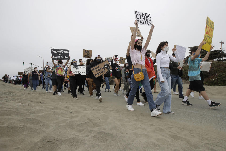 Gay activists and suppoters march on the Great Highway at Ocean Beach in San Francisco, Sunday, June 14, 2020, at a protest over the Memorial Day death of George Floyd, who died after being restrained by Minneapolis police. (AP Photo/Jeff Chiu)