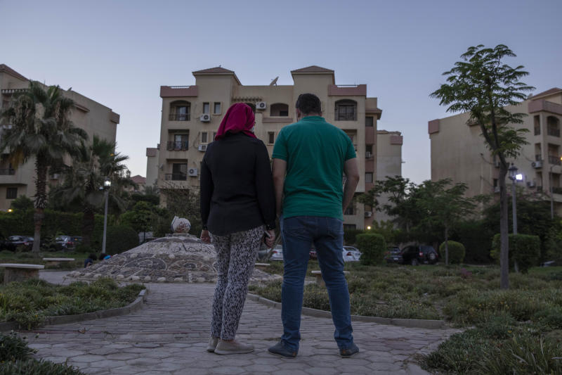 Noha, an Egyptian engineer, and her husband Ahmed, who were chosen to be among the U.S. government's roughly 50,000 visa lottery winners this year, pose for a photograph near their home in Cairo, Egypt, Tuesday, June 30, 2020. While visas for Noha and her children came in February, Ahmed's has not arrived and now they fear it may never come. President Donald Trump in June halted visas from being issued outside the United States through the end of the year. (AP Photo/Nariman El-Mofty)