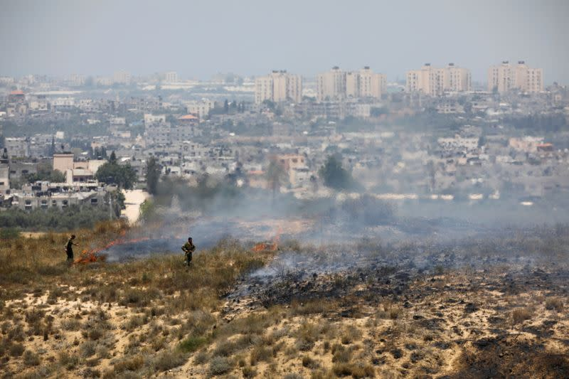 FILE PHOTO: Israeli soldiers are seen near fire burns in scrubland near the Gaza Strip, in an area where Palestinians have been causing blazes by flying kites and balloons loaded with flammable material across the border between Israel and the Gaza Strip