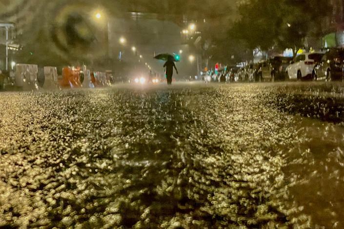 A person on foot braves the rain Wednesday in the Bronx borough of New York City.