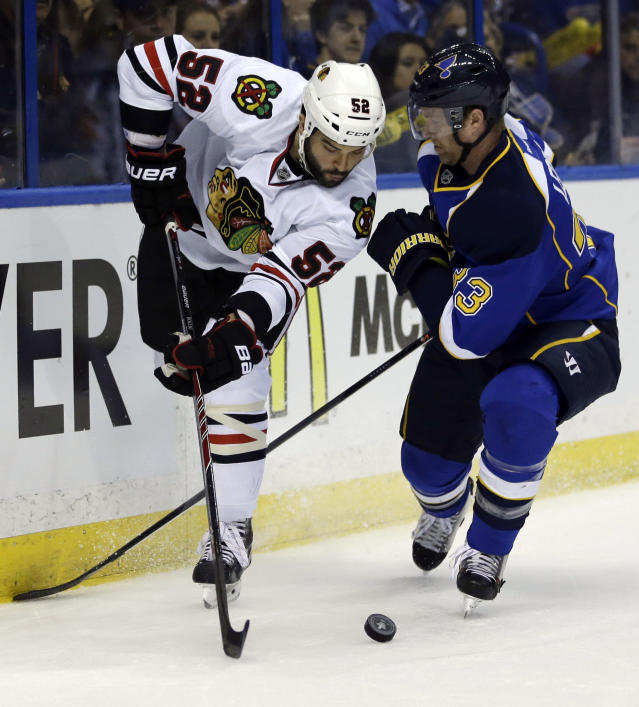 Chicago Blackhawks' Brandon Bollig, left, passes the puck as St. Louis Blues' Jordan Leopold defends during the first period in Game 5 of a first-round NHL hockey playoff series Friday, April 25, 2014, in St. Louis. (AP Photo/Jeff Roberson)