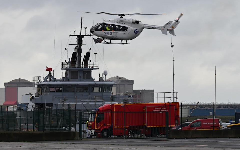 A French Urgent Medical Aid Service helicopter landing at Dunkerque port, northern France, after a boat carrying migrants capsized off the coast - DENIS CHARLET/AFP