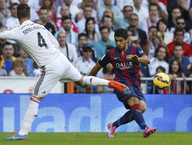 "Barcelona's Luis Suarez (R) kicks the ball past Real Madrid's Sergio Ramos during their Spanish first division ""Clasico"" soccer match at the Santiago Bernabeu stadium in Madrid October 25, 2014. REUTERS/Sergio Perez (SPAIN - Tags: SOCCER SPORT)"