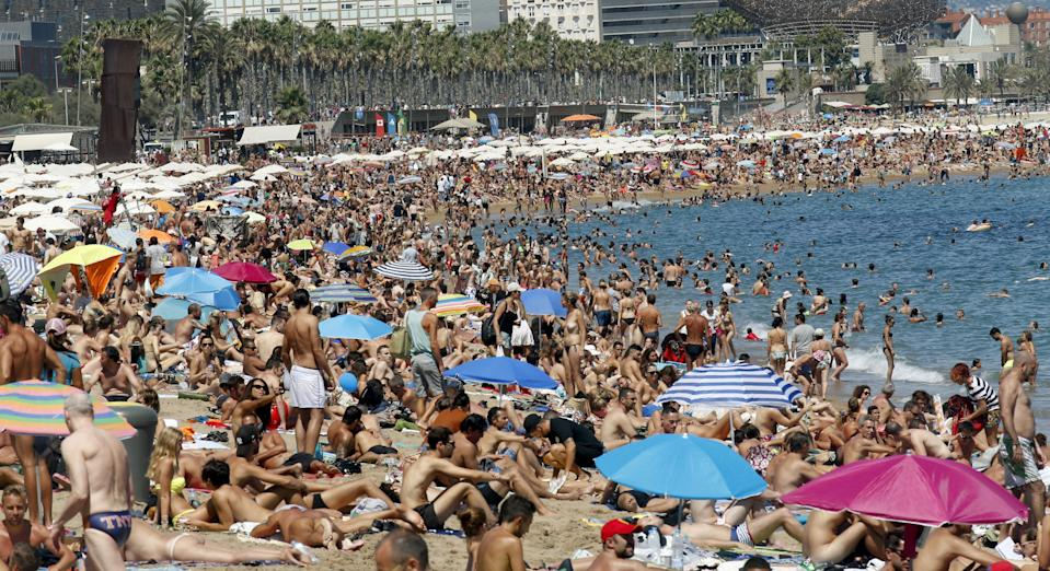 People cool off at Sant Sebastia beach in Barceloneta neighbourhood in Barcelona, Spain, August 16, 2015. Spanish consumer prices rose slightly in July from a year earlier, the second increase in a row as the economy strengthened and retailers and hotels hiked their charges. The prices of package holidays were up from a year ago in July, National Statistics Institute (INE) said. Hotel, cafe and restaurant prices were up 0.9 percent year-on-year in July when the summer tourism season got underway. REUTERS/Albert Gea      TPX IMAGES OF THE DAY