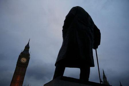 A statue of former British Prime Minister Winston Churchill stands in front of a view of the Houses of Parliament in London