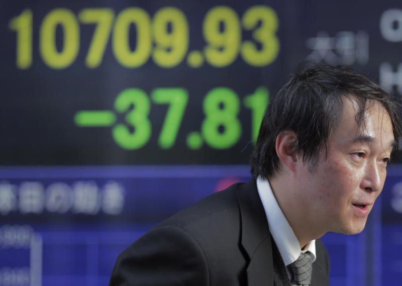 A man walks by the electronic stock board of a securities firm showing Japan's Nikkei 225 index fallen 37.81 points to 10709.93 in Tokyo, Tuesday, Jan. 22, 2013. Asian stock markets wavered between gains and losses Tuesday after Japan's central bank ceded to political pressure and announced stimulus measures aimed at extricating the country from years of economic malaise.(AP Photo/Itsuo Inouye)