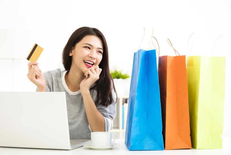 A young woman holding her credit card as she gazes at shopping bags.