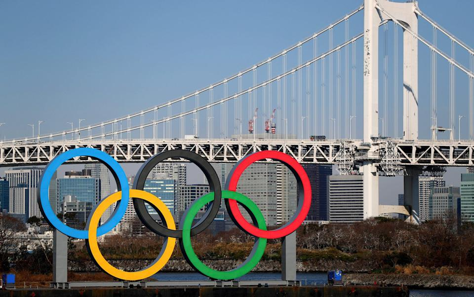The Olympic rings are seen in front of Tokyo's iconic Rainbow Bridge and Tokyo Tower at Odaiba Marine Park on January 20, 2020 in Tokyo - Composer who abused disabled classmates and forced them to carry out sex acts will still feature in Olympics opening ceremony - GETTY IMAGES