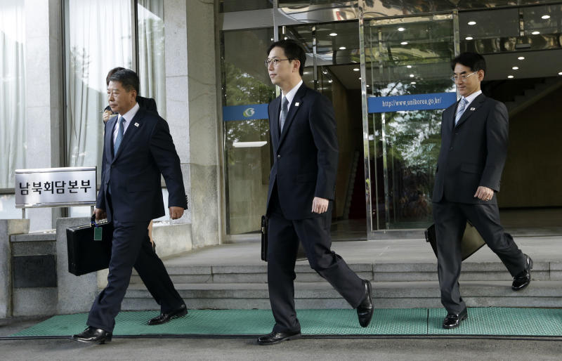 Chun Hae-sung, center, the head of South Korea's working-level delegation, walks with delegates Kwon Young-yang, left, and Kang Jong-won as they leave for Panmunjom at the Office of the South Korea-North Korea Dialogue in Seoul, South Korea, Sunday, June 9, 2013. North and South Korea will meet in the village straddling their heavily armed border Sunday for the first government-level talks on the peninsula in more than two years as they try to lower tension and restore stalled projects that once symbolized their rapprochement. (AP Photo/Lee Jin-man)