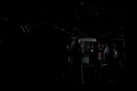 People walk at the parking garage of a building as they evacuate it during a blackout in Caracas, Venezuela March 25, 2019. REUTERS/Carlos Garcia Rawlins