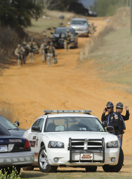 Police SWAT teams and hostage negotiators are gathered at standoff and hostage scene in Dale County near Midland City, Ala. on Wednesday Jan. 30, 2013. Authorities were locked in a standoff Wednesday with a gunman authorities say on Tuesday intercepted a school bus, killed the driver, snatched a 6-year-old boy and retreated into a bunker at his home in Alabama. (AP Photo/Montgomery Advertiser, Mickey Welsh) (AP Photo/The Montgomery Advertiser, Mickey Welsh)