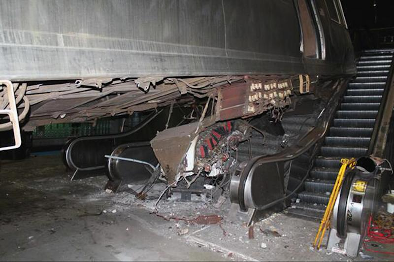 """This photo released Tuesday, March 25, 2014, by the National Transportation Safety Board shows the aftermath of a Chicago commuter train that crashed Monday at O'Hare International Airport when the train jumped off the tracks and climbed an escalator. An NTSB official said Wednesday that the operator of the train admitted she """"dozed off"""" before the accident. (AP Photo/Courtesy of the National Transportation Safety Board)"""