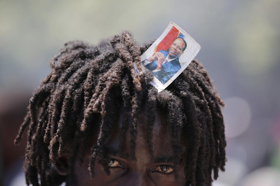 A supporter of former Haitian President Jean-Bertrand Aristide looks into the camera as he waits with others near the airport for his expected arrival from Cuba, where he underwent medical treatment, in Port-au-Prince, Haiti, Friday, July 16, 2021. Aristide's return adds a potentially volatile element to an already tense situation in a country facing a power vacuum following the July 7 assassination of President Jovenel Moïse. (AP Photo/Fernando Llano)