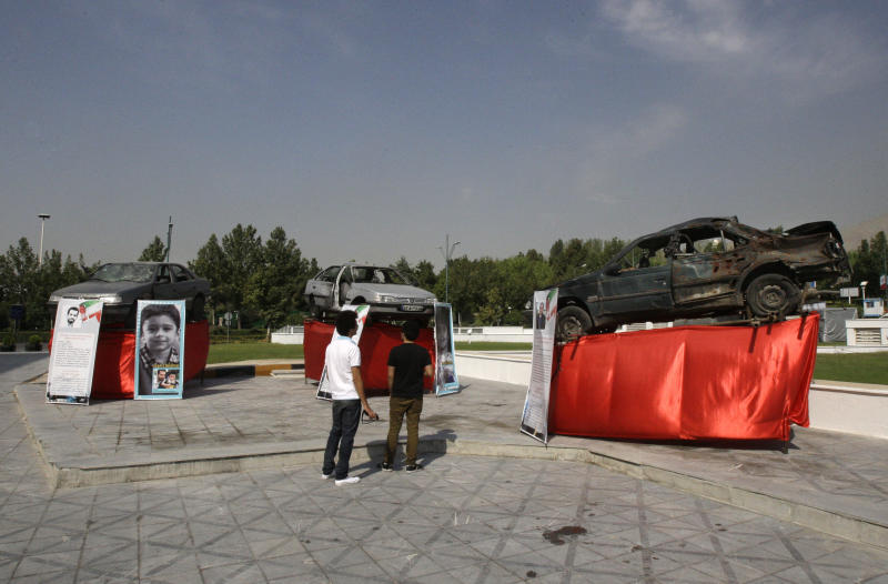 Damaged cars that three Iranian scientists, Masoud Ali Mohammadi, right, Majid Shahriari, center, and Mostafa Ahmadi Roshan, were riding in when they were killed in bombings over the last three years are displayed outside a conference hall hosting the meeting of Non-Aligned Movement, NAM, in Tehran, Iran, Sunday, Aug. 26, 2012. Iran says the attacks against its scientists are part of a covert campaign by Israel and the West to sabotage its nuclear program, which the U.S. and its allies suspect is aimed at producing nuclear weapons. Posters show some of the slain scientist's children who were not killed. (AP Photo/Vahid Salemi)