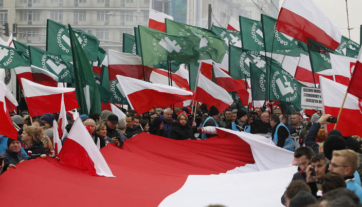 Members of radical right-wing groups wave flags during a march by tens of thousands of people and hosted by President Andrzej Duda that marked 100 years since Poland regained independence in Warsaw, Poland, Sunday, Nov. 11, 2018. (AP Photo/Czarek Sokolowski)