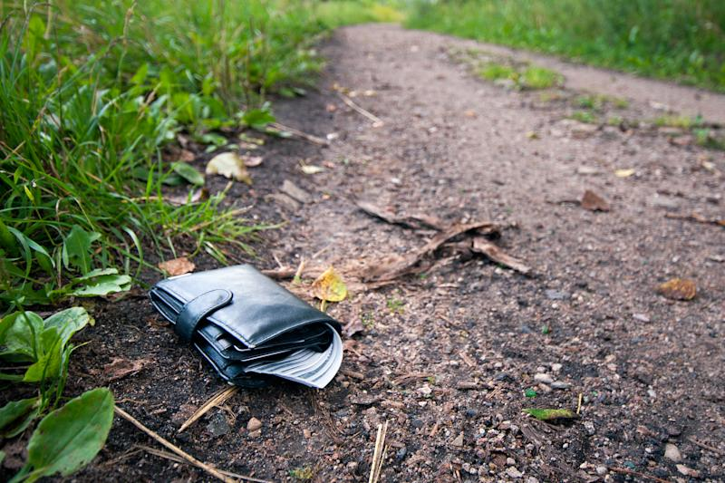 A file picture of a black leather wallet on a path.