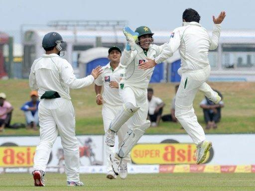 Pakistan's Saeed Ajmal (right) celebrates with wicketkeeper Adnan Akmal (2nd right) after the dismissal of Sri Lanka's Tharanga Paranavitana during the first day of the opening Test match at the Galle International Stadium. Tillakaratne Dilshan and Kumar Sangakkara have hammered centuries as Sri Lanka walloped Pakistan on the opening day of the first cricket Test in Galle