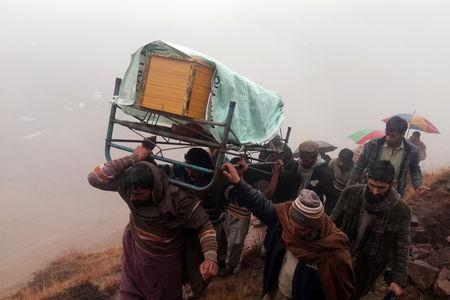 Men and relatives carry the coffin of Sudheer Qureshi, a boy whom mourners say was killed by shelling fired from Indian Administered Kashmir, during a funeral in Jehlum Valley in Pakistan Administered Kashmir, Pakistan