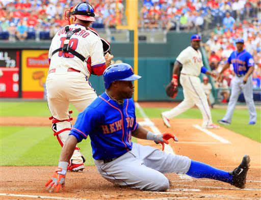New York Mets' Eric Young scores on a sacrifice fly ball by Marlon Byrd while Philadelphia Phillies catcher Humberto Quintero looks to throw to second during the first inning of a baseball game on Sunday, June 23, 2013, in Philadelphia. (AP Photo/Tom Mihalek)