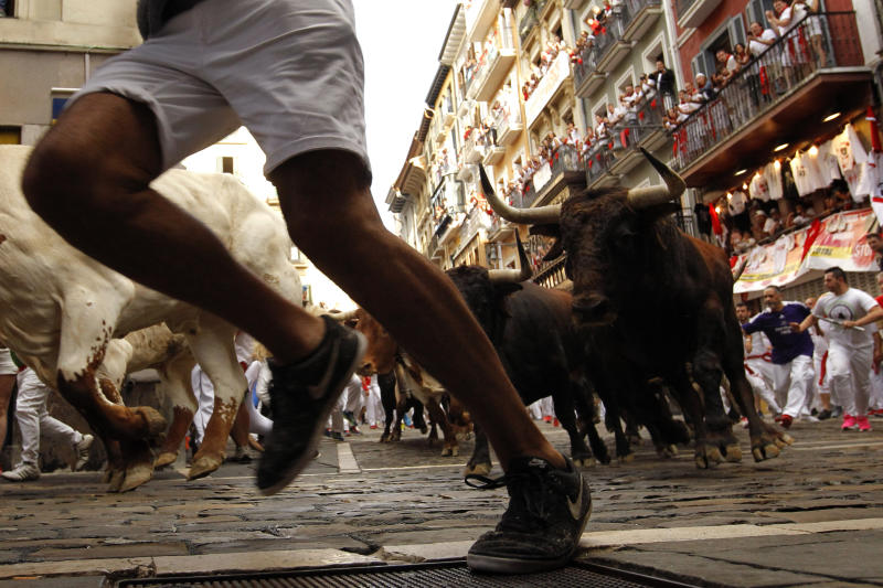 Revellers run next to fighting bulls from Cebada Gago ranch, during the running of the bulls at the San Fermin on July 8, 2019. (Photo: Alvaro Barrientos/AP)