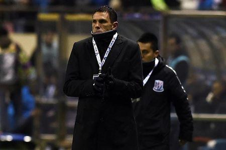 Gustavo Poyet, coach of Shanghai Shenhua, stands near the field during the AFC Champions League 2017 play-off match between Shanghai Shenhua and Brisbane Roar in Shanghai