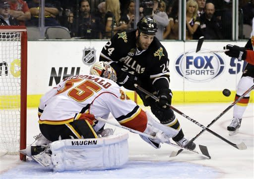 Calgary Flames goalie Joey MacDonald (35) deflects a shot by Dallas Stars left wing Eric Nystrom (24) in the first period of an NHL hockey game Monday, March 18, 2013, in Dallas. (AP Photo/Tony Gutierrez)