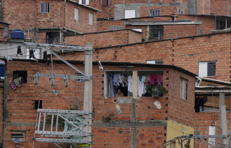 A resident is framed by laundry hanging out to dry in the Paraisopolis favela, during the community's centennial celebration, in Sao Paulo, Brazil, Thursday, Sept. 16, 2021. One of the largest favela's in Brazil, home to tens of thousands of residents in the country's largest and wealthiest city, Paraisopolis is grappling with crime and a pandemic that have challenged daily life for many who live there, but organizers say its people have built a vibrant community and are launching a 10-day celebration of its achievements. (AP Photo/Andre Penner)