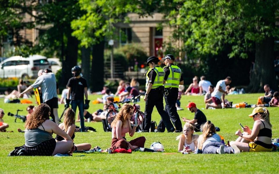 Police Scotland officers walking among large numbers of sunbathers gathered at The Meadows close to the centre of Edinburg - Stuart Nicol