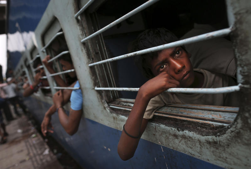 A young Indian boy watches from a window of a stalled train as he waits for the train to resume its services following a power outage at a railway station in New Delhi, India, Tuesday, July 31, 2012. India's energy crisis cascaded over half the country Tuesday when three of its regional grids collapsed, leaving 620 million people without government-supplied electricity for several hours in, by far, the world's biggest blackout. Hundreds of trains stalled across the country and traffic lights went out, causing widespread traffic jams in New Delhi. (AP Photo/Kevin Frayer)