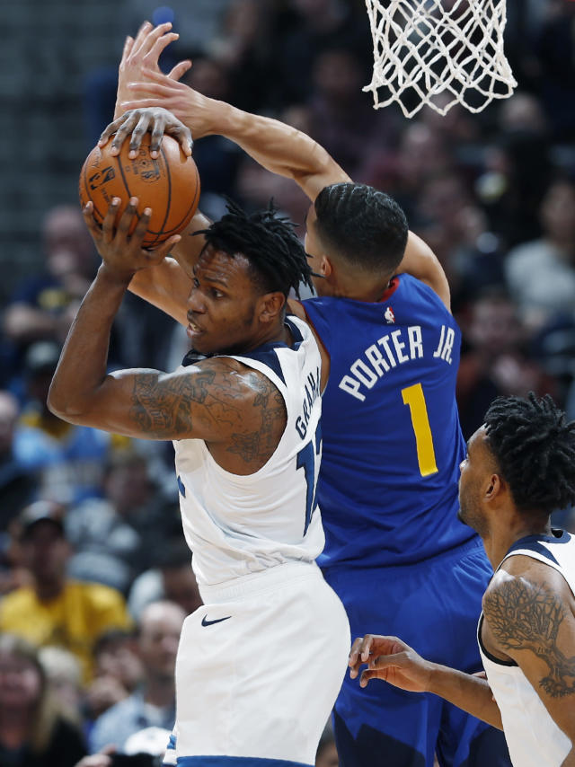 Minnesota Timberwolves guard Treveon Graham, left, pulls in a rebound in front of Denver Nuggets forward Michael Porter Jr. (1) in the first half of an NBA basketball game Friday, Dec. 20, 2019, in Denver. (AP Photo/David Zalubowski)