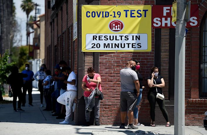 People stand in line at a clinic offering quick coronavirus testing near Long Beach, California.