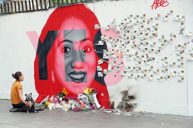 A woman kneels infront of a mural of Savita Halappanavar in Dublin