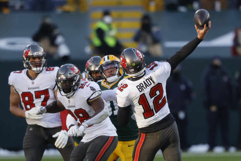 Tampa Bay Buccaneers quarterback Tom Brady (12) throws a 29-yard touchdown pass to Buccaneers' Scott Miller against the Green Bay Packers during the first half of the NFC championship NFL football game in Green Bay, Wis., Sunday, Jan. 24, 2021. (AP Photo/Jeffrey Phelps)