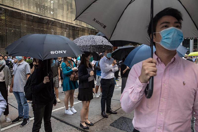 "Protesters and office workers gather during a protest in the Central district in Hong Kong on November 13, 2019. - Pro-democracy protesters stepped up on November 13 a ""blossom everywhere"" campaign of road blocks and vandalism across Hong Kong that has crippled the international financial hub this week and ignited some of the worst violence in five months of unrest. (Photo by DALE DE LA REY / AFP) (Photo by DALE DE LA REY/AFP via Getty Images)"