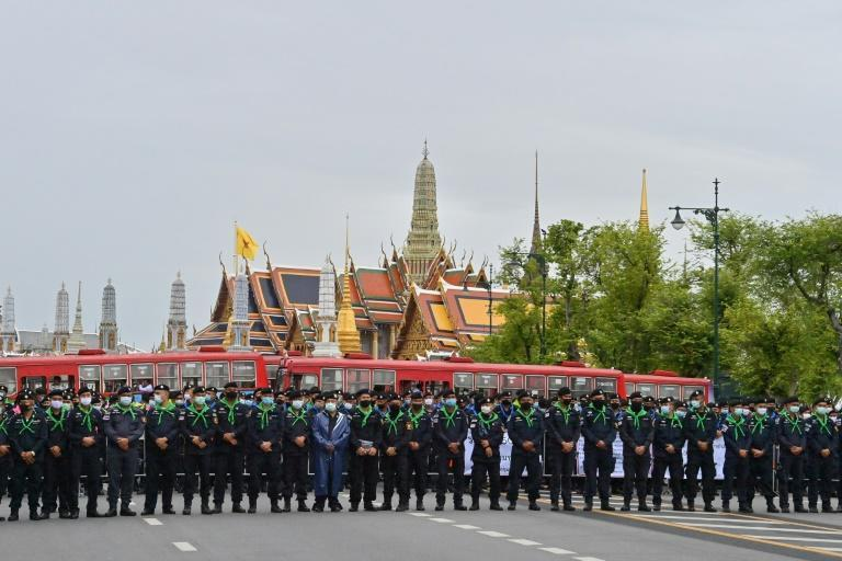 A line of police stand guard in front of the Grand Palace as anti-government protesters take part in a pro-democracy rally in Bangkok