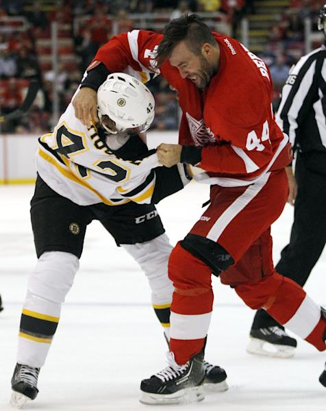Boston Bruins defenseman Mike Moore, left, and Detroit Red Wings right wing Todd Bertuzzi (44) fight during the first period of a preseason NHL hockey game Saturday, Sept. 21, 2013, in Detroit. (AP Photo/Duane Burleson)