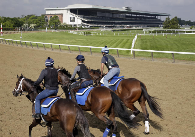 FILE- In this June 6, 2019, file photo, riders workout with horses at Belmont Park in Elmont, N.Y. After a 4-year-old colt exhibited fever and neurological symptoms on Saturday, June 27, 2020, a barn at Belmont Park has been placed under a precautionary quarantine because of a suspected case of equine herpesvirus Type 1. (AP Photo/Seth Wenig)