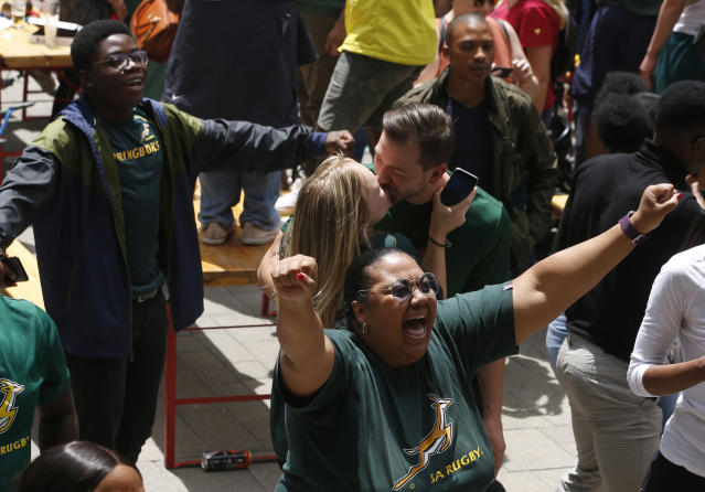 South Africa fans watching a giant screen at the Nelson Mandela Square in Johannesburg, South Africa, celebrate South Africa scoring points during the Rugby World Cup final between South Africa and England being played in Tokyo, Japan on Saturday Nov. 2, 2019. South Africa defeated England 32-12. (AP Photo/Denis Farrell)