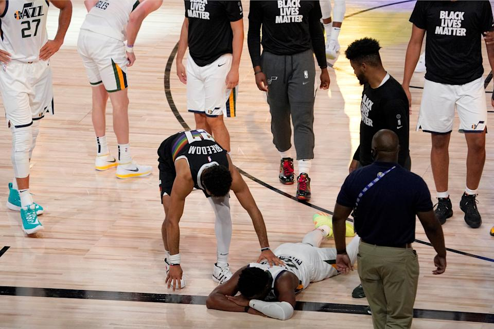 Denver Nuggets' Jamal Murray, center left, reaches down to console Utah Jazz's Donovan Mitchell (45), on floor, after the Nuggets 80-78 win during an NBA first round playoff basketball game, Tuesday, Sept. 1,2020, in Lake Buena Vista, Fla. (AP Photo/Mark J. Terrill) ORG XMIT: TXTG188