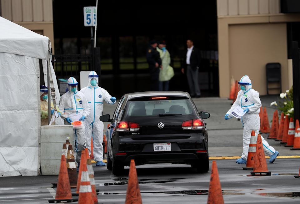 SAN MATEO, CALIFORNIA - MARCH 16: Medical personnel surround a car that is going through a coronavirus drive-thru test clinic at the San Mateo County Event Center on March 16, 2020 in San Mateo, California. Drive-thru test clinics for COVID-19 are popping up across the country as more tests become available. (Photo by Justin Sullivan/Getty Images)