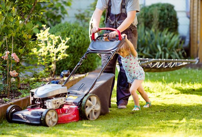 Happy little toddler girl and middle-aged father with lawn mower. Family, daughter, preschool child and dad cut the lawn. Portrait of family working in garden, trimming grass. Garden works in summer