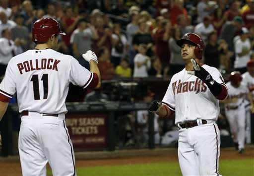 Arizona Diamondbacks' Martin Prado, right, gets a high-five from teammate A.J. Pollock (11) after scoring a run against the Pittsburgh Pirates during the third inning in a baseball game, on Monday, April 8, 2013. (AP Photo/Ross D. Franklin)