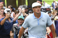 Spectators run up behind Bryson DeChambeau after he shot from the rough on the eighth hole during the third round of the BMW Championship golf tournament, Saturday, Aug. 28, 2021, at Caves Valley Golf Club in Owings Mills, Md. (AP Photo/Terrance Williams)