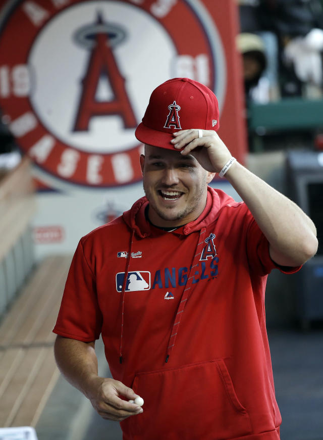 Los Angeles Angels' Mike Trout jokes with teammates in the dugout before the start of a baseball game against the Houston Astros, Monday, July 15, 2019, in Anaheim, Calif. (AP Photo/Marcio Jose Sanchez)