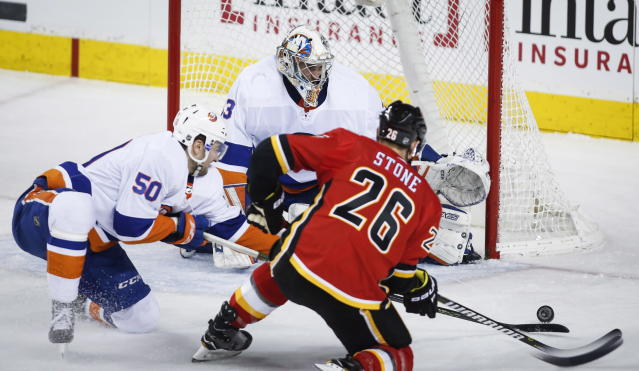 New York Islanders' Adam Pelech, left, helps goalie Christopher Gibson, center, of Finland, by swatting the puck away from Calgary Flames' Michael Stone during second-period NHL hockey game action in Calgary, Alberta, Sunday, March 11, 2018. (Jeff McIntosh/The Canadian Press via AP)