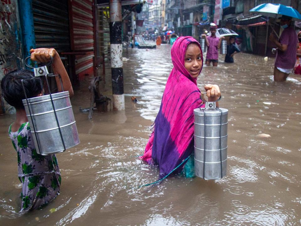 Children carrying tiffin boxes through a flooded street in Dhaka, Bangladesh last week: EPA/MONIRUL ALAM